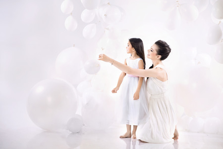 Mom and cute daughter playing balloons Stock Photo