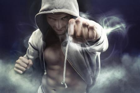 Boxer muscular com capuz perfurando um inimigo
