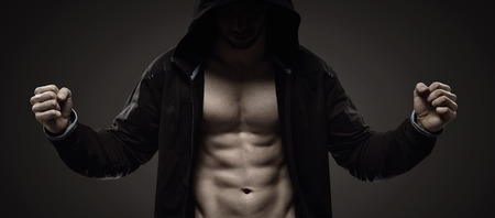 Strong hooded man making muscles Stock Photo