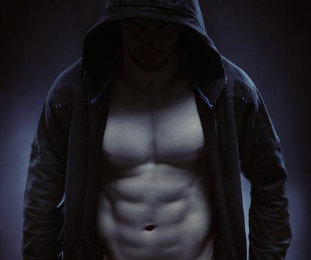 modelos hombres: Hombre fuerte con capucha hidiing a s� mismo en la oscuridad