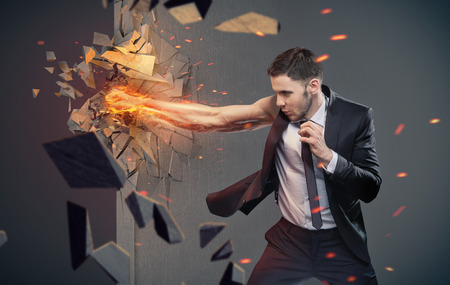 beating: Conceptual portrait of a clever businessman beating a barrier Stock Photo