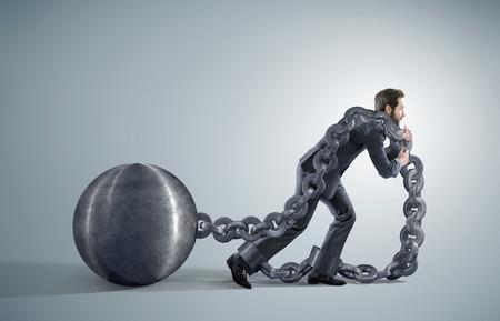 Hombre de negocios agotado arrastrando pesadas cadenas