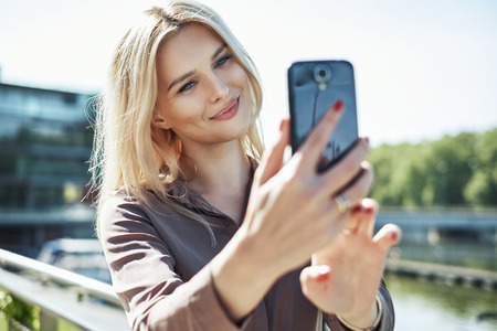 Portrait of a blond lady taking a selfie Stock Photo