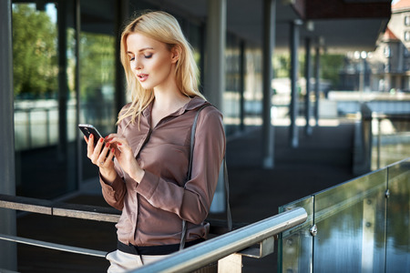 new generation: Blond lady using her new generation smartphone Stock Photo