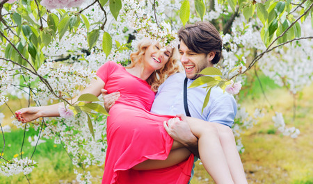 Joyful couple in the fragrant apple orchard Banque d'images