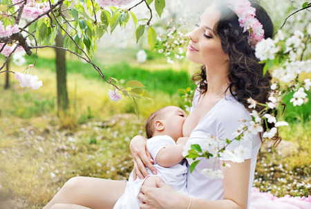 Mother feeding a baby in the spring orchard