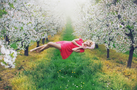 Majestic slim nymph levitating in the colorful orchard photo
