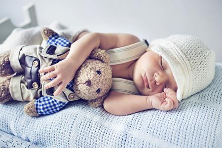 recien nacido: Niño recién nacido que duerme con un juguete del oso de peluche