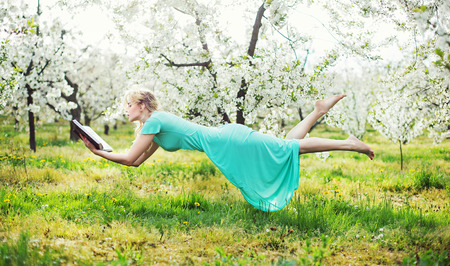 Adorable lady levitating during book reading photo