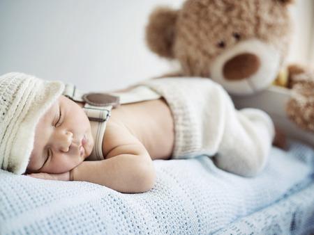 recien nacido: Ni�o reci�n nacido que duerme con un oso de peluche