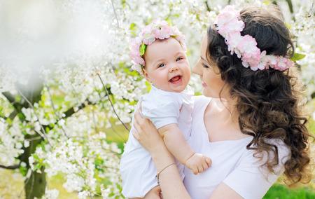 Jonge moeder en haar kleine baby ontspannen in het voorjaar een boomgaard