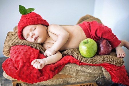tot: Cute newborn child sleeping on a soft red blanket