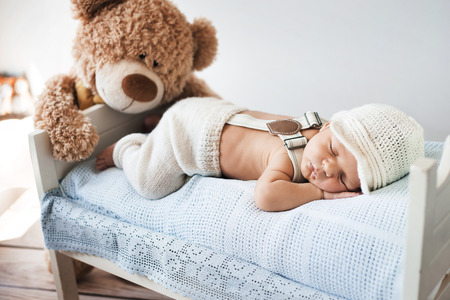 Newborn child sleeping with a teddy bear