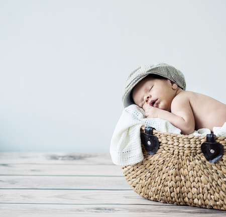 Cute tot sleeping in a wicker basket