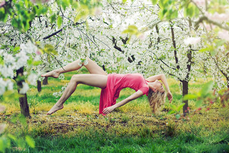 Adorable slim lady levitating in the colorful orchard photo