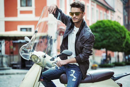 bel homme: Portrait d'un beau jeune homme sur une moto Banque d'images