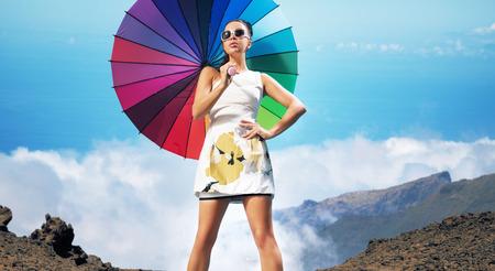 Hermosa morena sensual que sostiene el paraguas colorido