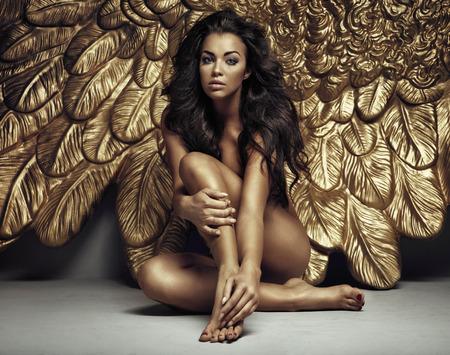 Portret van een sexy engel met gouden vleugels Stockfoto