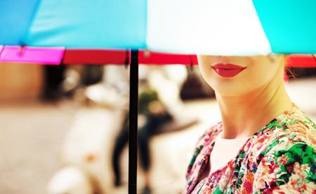 カラフルな傘を保持している美しい女性 写真素材