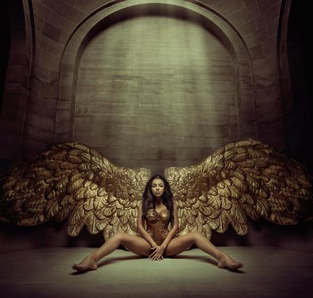 Powabna złota anioł w ciemnym korytarzu Zdjęcie Seryjne