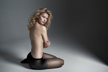 nude blond: Half nude blond woman wearing black panty hose Stock Photo