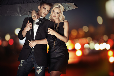 male fashion: Smart couple walking with the black umbrella Stock Photo