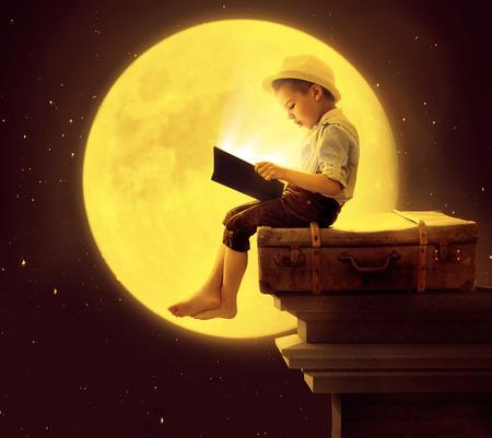 Criança bonito que lê um livro na luz de lua