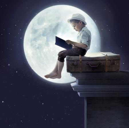 Portrait d'un petit garçon lisant un conte de fées