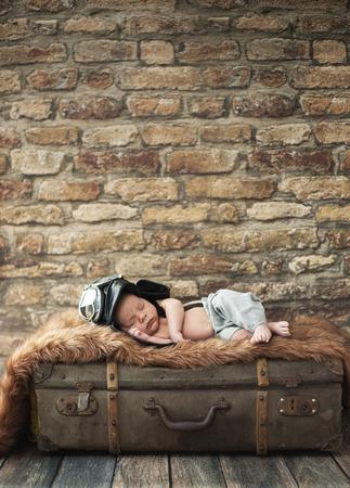 baby sleep: Little pilot boy sleeping on the luggage