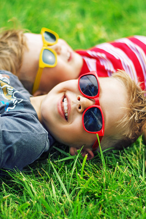 one little boy: Cheerful brothers lying on the fresh lawn Stock Photo