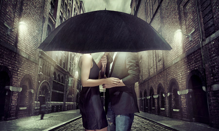 Pares alegres escondiéndose bajo el paraguas