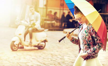 Retrato de una mujer joven sosteniendo un paraguas de colores