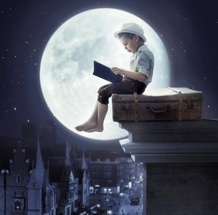 Malý chlapec seděl na koženém zavazadla