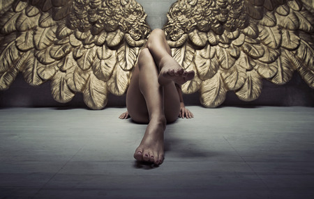 angel girl: Picture of a gold angel relaxing on the floor Stock Photo