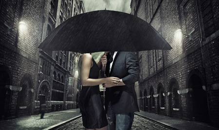 Adorable couple under the black umbrella