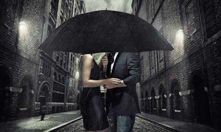 ao ar livre: Casal adorável sob o guarda-chuva preto Imagens