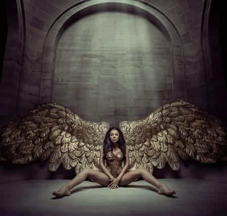 Brunette Frau sitzt auf dem dunklen Boden Lizenzfreie Bilder