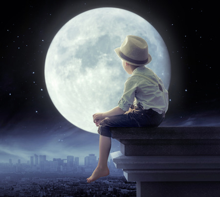 fairytale background: Little boy looking a the city in the night Stock Photo