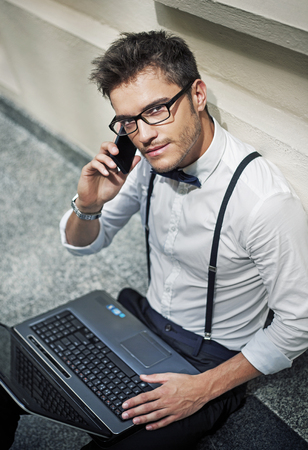 workaholic: Young handsome workaholic in the hotels lobby Stock Photo