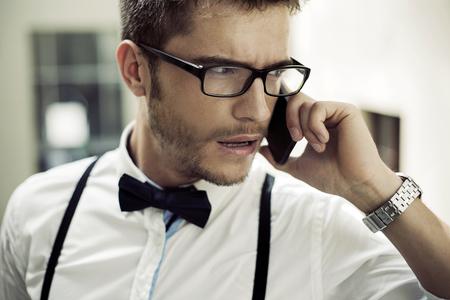 Ritratto del primo piano di un uomo d'affari telefonando photo