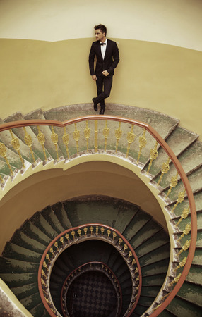 Handsome elegant man standing on the old fashioned stairs photo