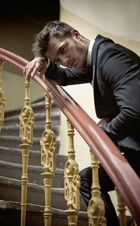 Uomo elegante leaing su un corrimano in legno photo