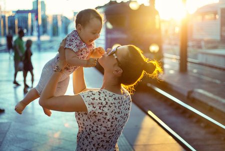 urban: Pretty mom carrying her little daughter Stock Photo