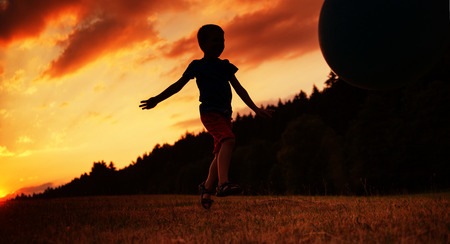 child ball: Small child playing ball on the field Stock Photo