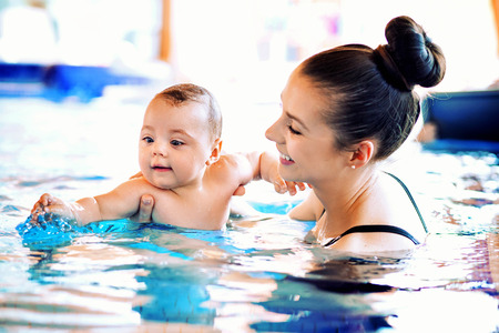 Pretty mother swimming her cute baby Banco de Imagens