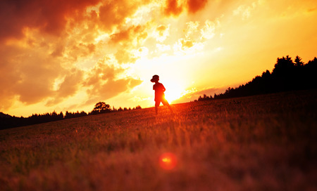 field sunset: Cheerful child playing football on the meadow