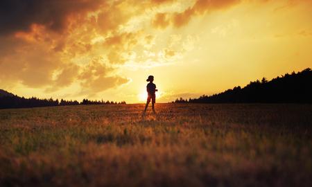 silueta niño: Silueta de niño feliz jugando en la pradera al atardecer Foto de archivo