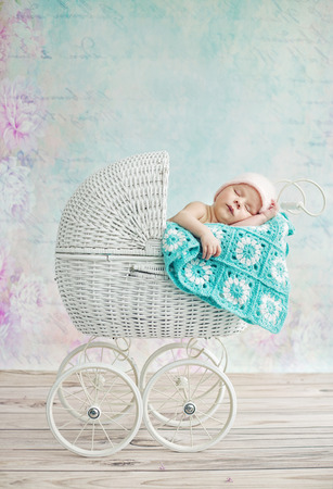 white dresses: Cute child sleeping in the wicker pram