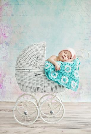petite fille avec robe: Mignon enfant endormi dans la poussette en osier Banque d'images