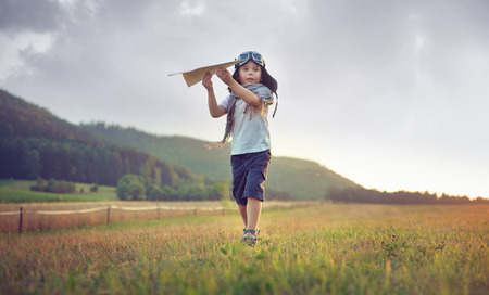 Cute little boy playing paper plane Stock Photo